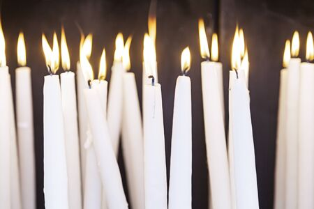 candle light: Lighted wax candles, lighted candles detail to pray Christian tradition, fee