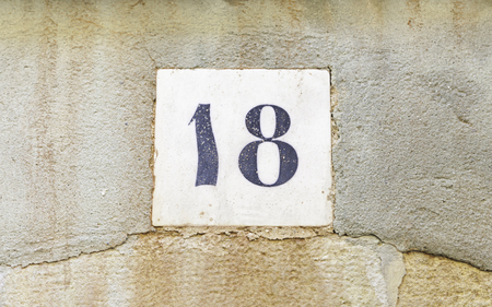 eighteen: Number eighteen in a wall, detail of a number of information on a wall of a house