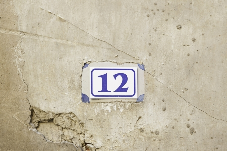 Number twelve on the wall, detail of a number of information on a wall, and figure number