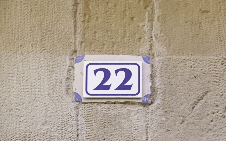 Number twenty-two on a wall, detail of a number of information in a house in the city photo