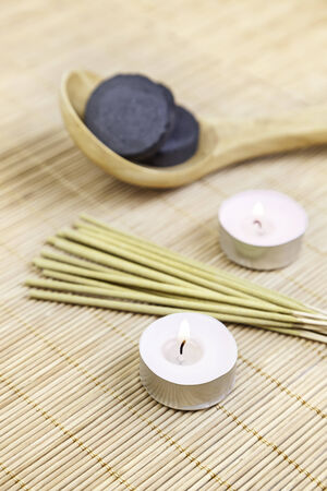 Candles and incense with charcoal, detail of decoration of a spa, relaxation and zen culture, aromatherapy
