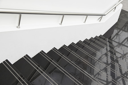 Black marble stairs, detail of stairs with metal railing and white, modern architecture, reflection and cleaning