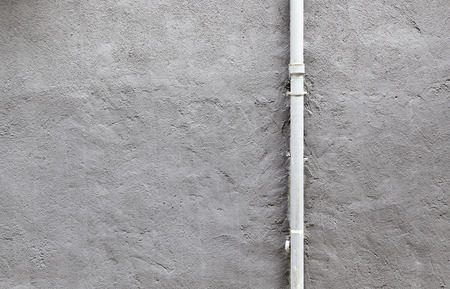 Pipe cement wall, detail of a wall painted with a metal pipe, outdoor exploration photo