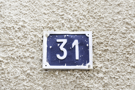 31: Number thirty-one on a wall, detail of a wall of a house with a number of information