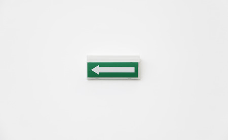 Green Arrow departure, detail of an arrow on a white wall, and safety information photo