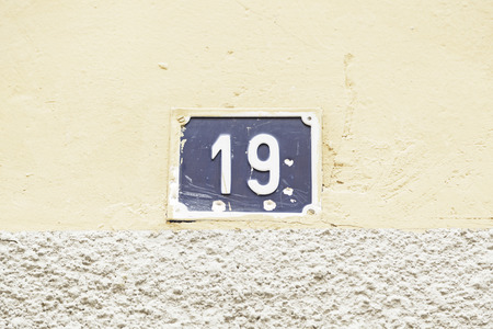 nineteen: Numero diciannove su una parete, dettaglio di un muro con numeri di informazioni, numeri dispari