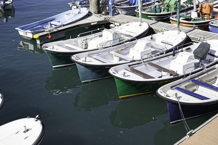 Boats moored at a marine dock, detail of recreational boats on a dock, fishing and fun, sea transport photo