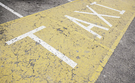 Taxi sign on asphalt, painted detail of a yellow road sign and safety information photo