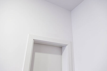 locked door: White door in a white wall, detail of a white painted wall with a locked door Stock Photo