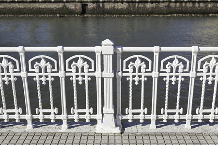 White metal railing, detail of a guardrail and decoration in the city photo
