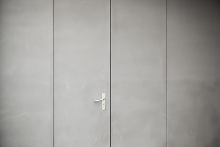 Gray metal door, detail of a closed metal door painted gray steel background texture photo