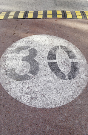 Traffic sign on asphalt, painted number thirty on the ground, speed limit sign. precaution and safety photo