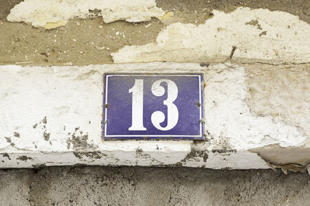 Number thirteen on a wall, detail of a number of information in a house photo
