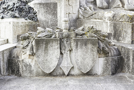 inquisition: Statue with shield and sword, detail of a war memorial statue, art in the city