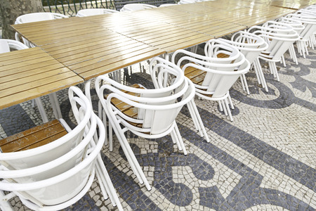 Terrace tables and chairs, detail of a land in a city street photo