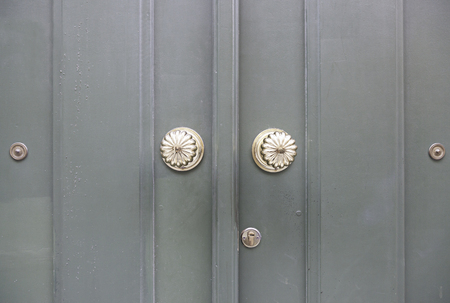 Wooden door with metal knockers, door detail of a decorated, safety and security photo