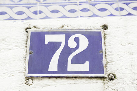 number plate: Number seventy-two on a wall, detail of a number of information on a plate in a house