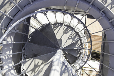 Old metal spiral staircase, detail of stairs up and down, old photo