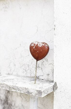 Red heart on marble, detail of a decorative heart on a marble tomb photo