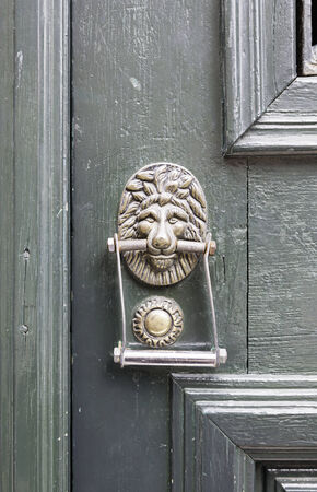 Old caller with a lion head, detail of a decorative bronze door photo