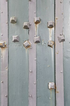 Old wooden door with metal nails, detail of a wooden door shabby textured background photo