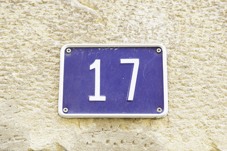 Number seventeen on the wall of a house, detail of a number of information, odd number photo
