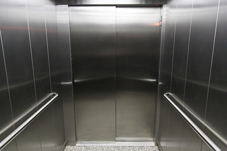 Interior of a metal elevator, detail of a modern stainless steel elevator, technology photo