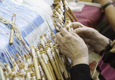 workroom: Traditional bobbin lace, detail of a women weaving, ancient tradition