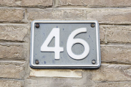 Number forty-six on the wall of a house, detail of a number of information, even number