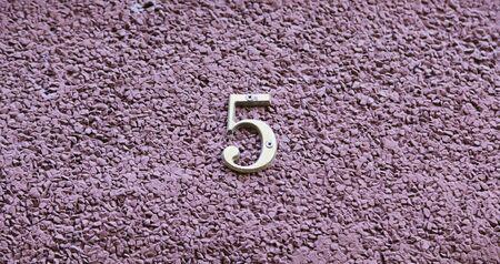 teclado numerico: El número cinco en la pared de una casa, detalle de un número de información, número impar Foto de archivo