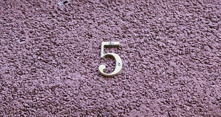 odd: Number five on the wall of a house, detail of a number of information, odd number