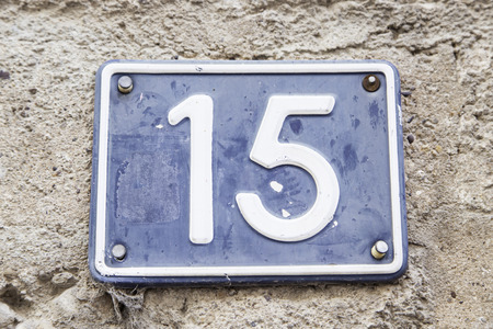 Number fifteen in a wall of a house, detail of a number of information, odd number Stock Photo