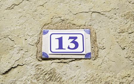 thirteen: Number thirteen on a wall, detail of a number of information, odd number, superstition Stock Photo