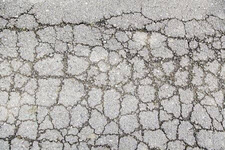 Cracked asphalt, detail of a damaged road and abandoned Фото со стока
