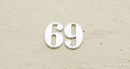 Number sixty nine on the wall of a house, detail of a number of information, odd number Stock Photo