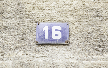 Number sixteen on the wall of a house, detail of a number of information photo
