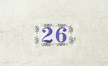 Number twenty-six on the wall of a house, detail of a number of information, even number photo