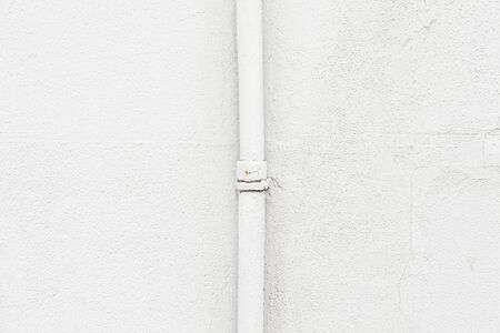 White wall with a pipe, detail of a textured wall photo