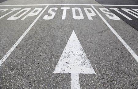 Stop sign on asphalt, detail of a traffic signal
