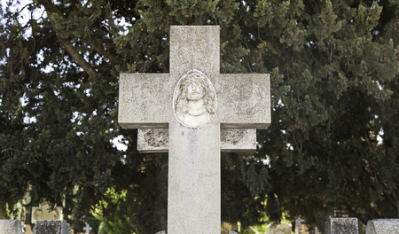 obituary: Religious cross on a grave, detail of an old cross in a cemetery Stock Photo