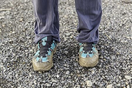 bedraggled: Muddy shoes, detail of a dirty and bedraggled pilgrim Stock Photo