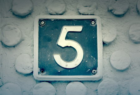 metal sign: Number five on the wall of a house, detail of a number of information, odd number