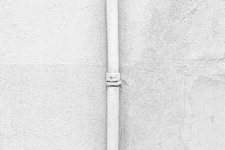 textured wall: White wall with a pipe, detail of a textured wall