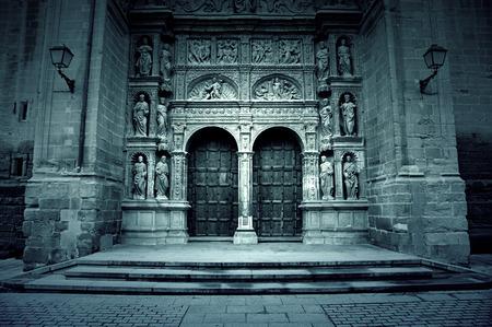 raperos: Fachada de la antigua iglesia medieval, detalle de una puerta de madera y esculturas góticas, City Tours