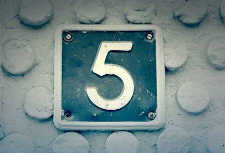 teclado numerico: El número cinco en la pared de una casa, detalle de una serie de información, número impar Foto de archivo