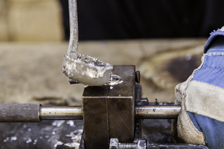crucible: Detail of metal cast to the heat, detail of handling and molding of metal