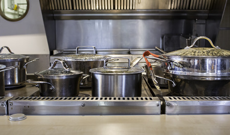 shiny black: Pans and pots preparing food in a kitchen, detail of an operating kitchen, cooking and preparing food Stock Photo