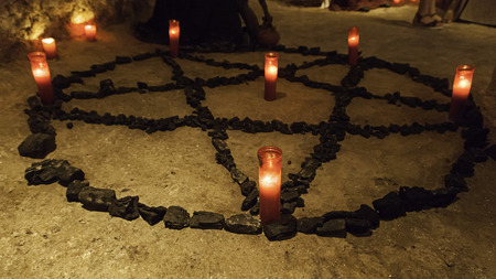 Satanic pentacle with lighted candles, dark magic ritual detail, occultism Stock Photo