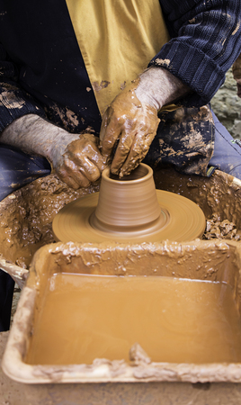 Hands of man working and shaping clay, potter in pottery, craft detail, creation