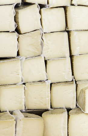 Chunks of cured cow cheese, detail of dairy product, market